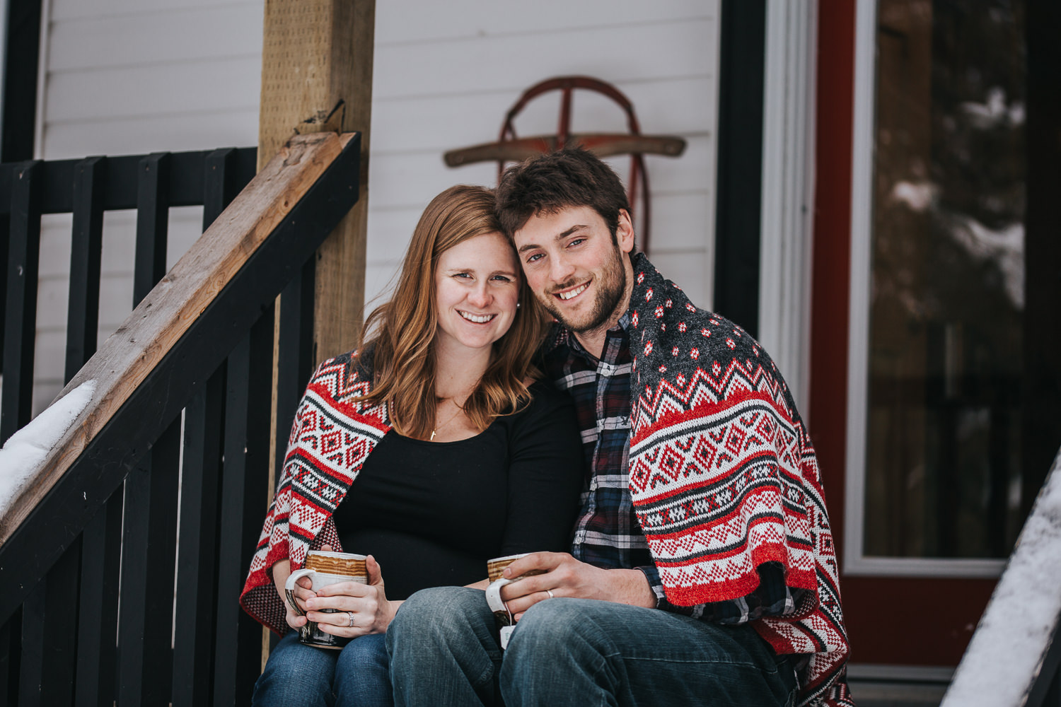 parents to be sitting on front porch steps wrapped in blanket looking at camera  - Uxbridge lifestyle photography