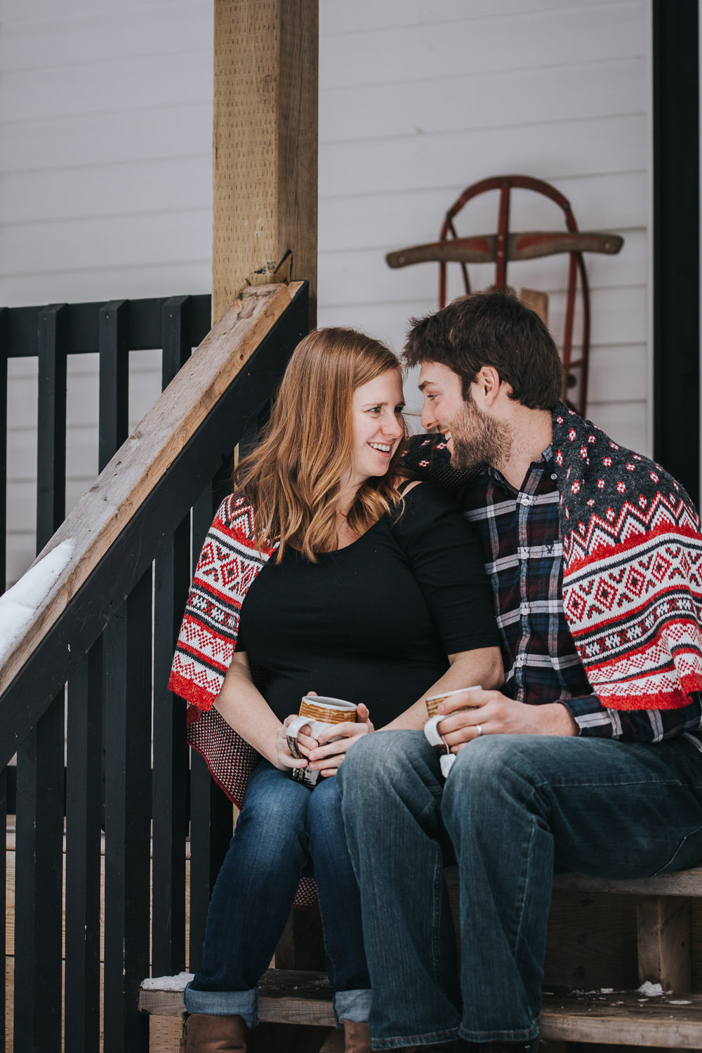 parents to be sitting on front porch steps wrapped in blanket looking at one another  - Newmarket lifestyle photos