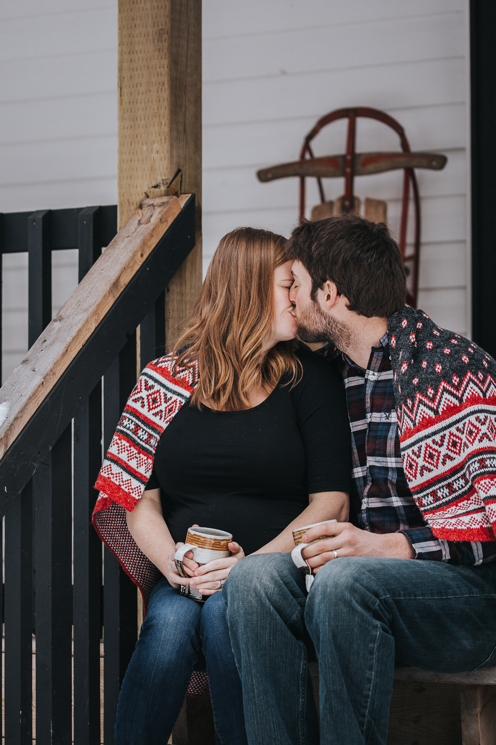 husband and pregnant wife kissing on front porch steps wrapped in blanket  - Stouffville lifestyle photography