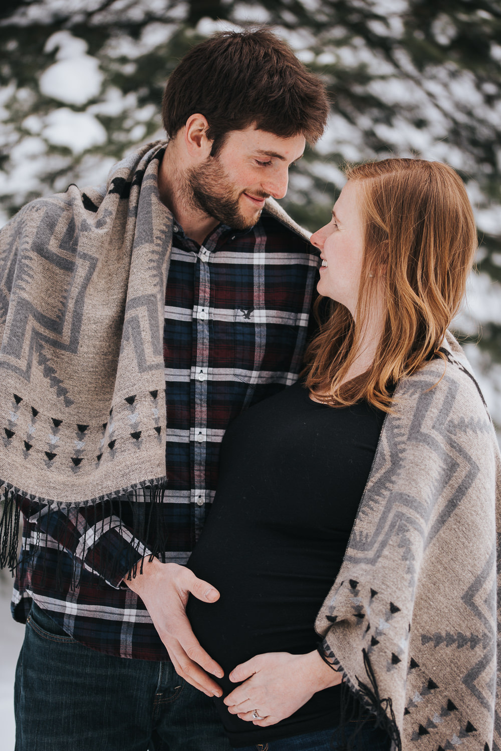 husband and wife smiling face-to-face and resting hands on pregnant mom's baby bump - Newmarket lifestyle photos
