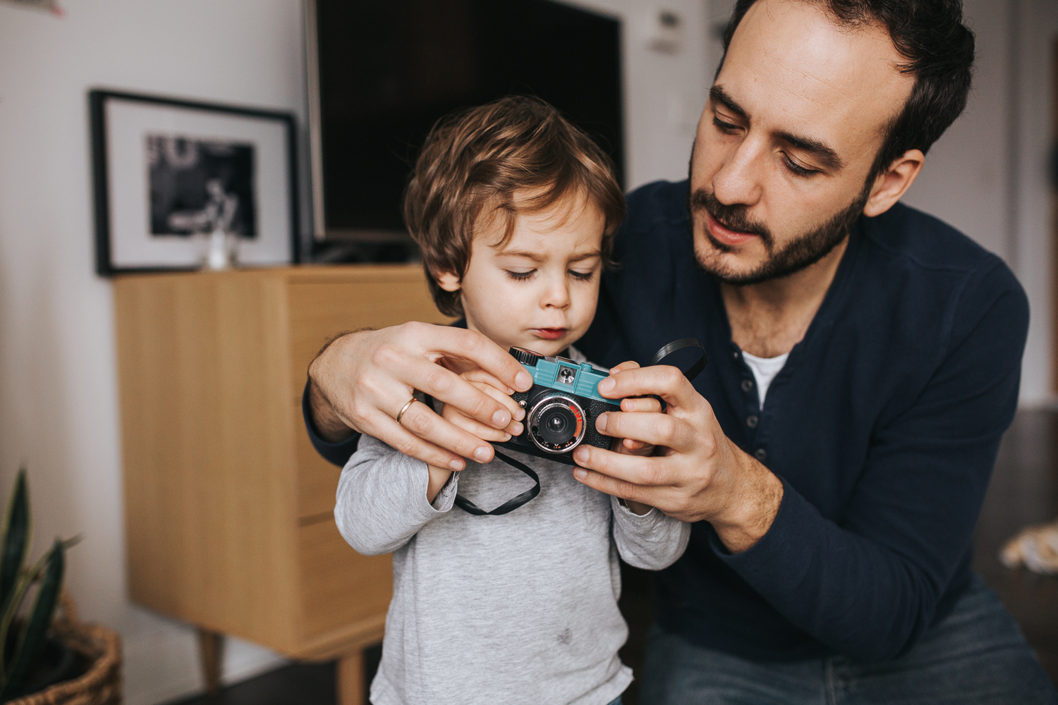 father helping 2 year old toddler boy with toy camera - newmarket family photography