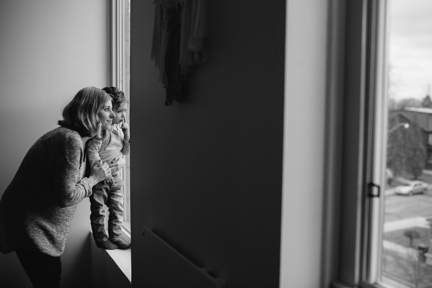 pregnant mom looks out window with 2 year old toddler son - uxbridge in-home family photography