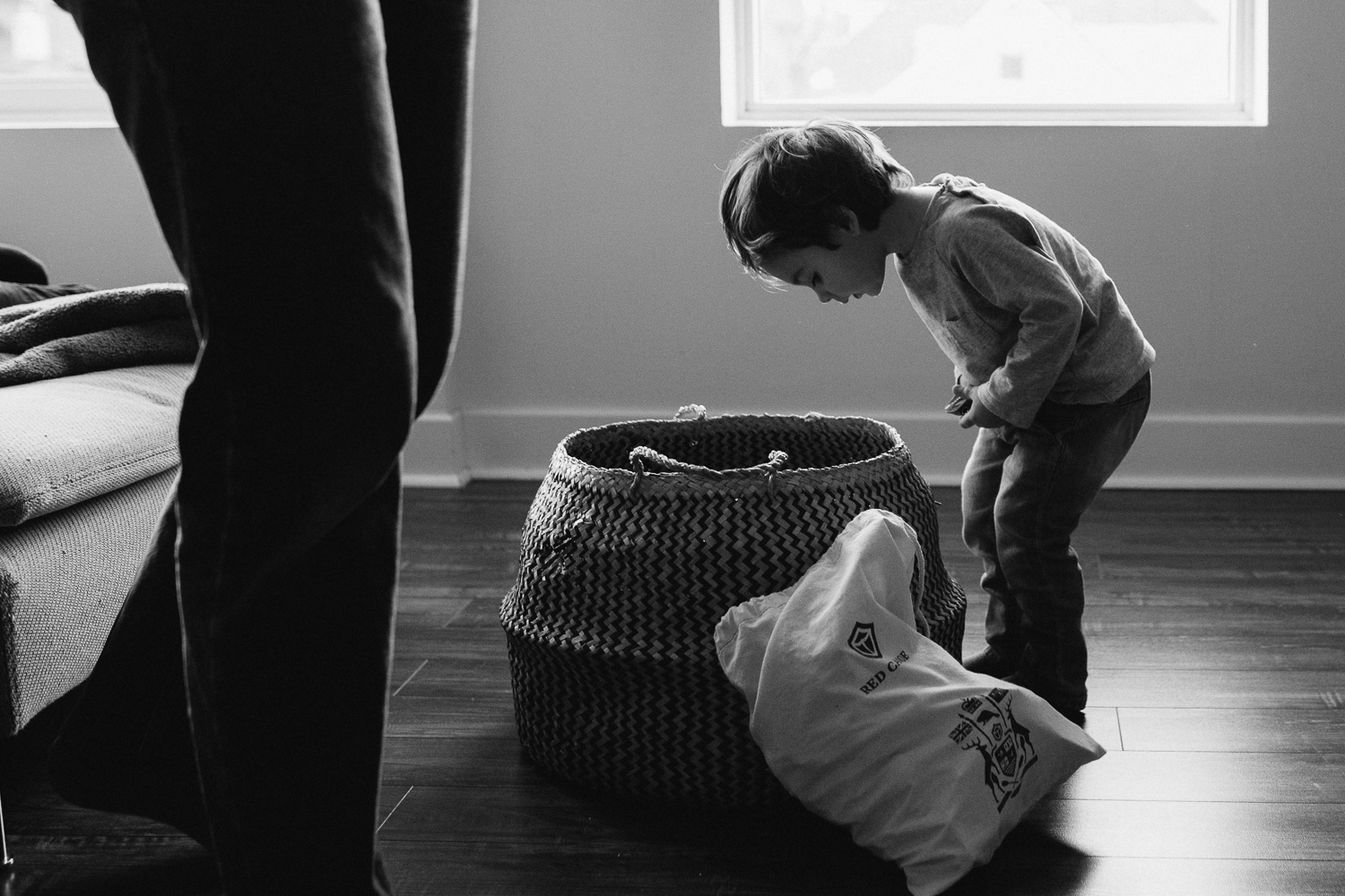 2 year old brunette toddler boy looks into basket for toys - uxbridge in-home family photos