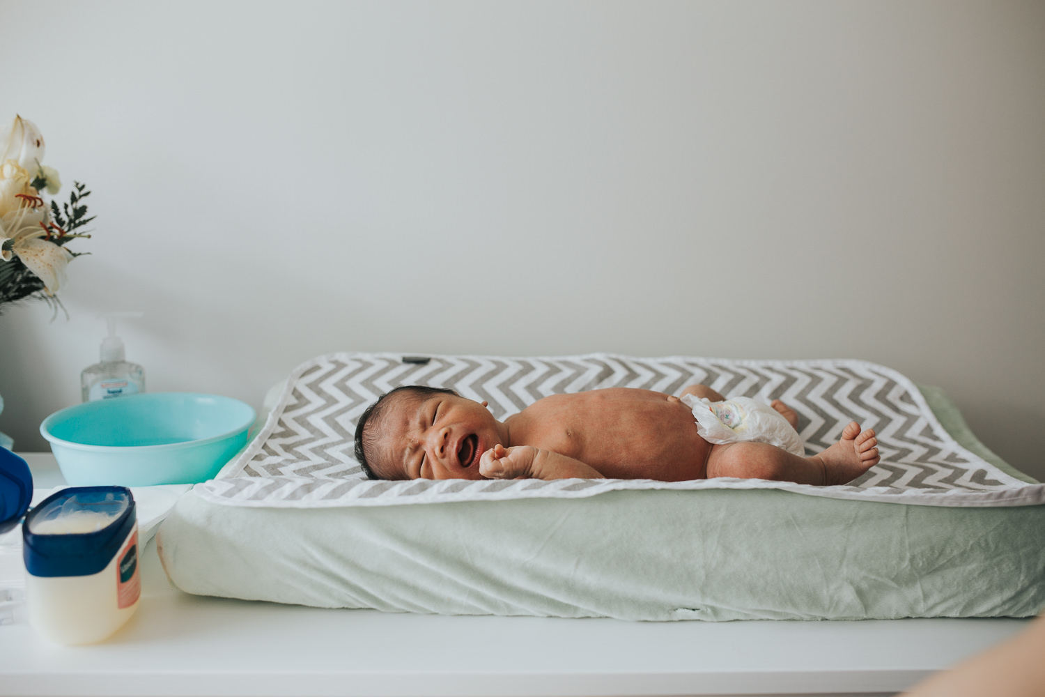 2 week old baby boy lying on green changing pad in diaper - Markham in-home photos