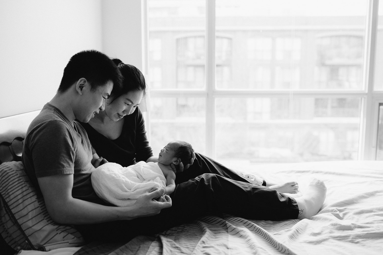 new parents snuggle and look at 2 week old baby boy while sitting in bed - Barrie lifestyle photography