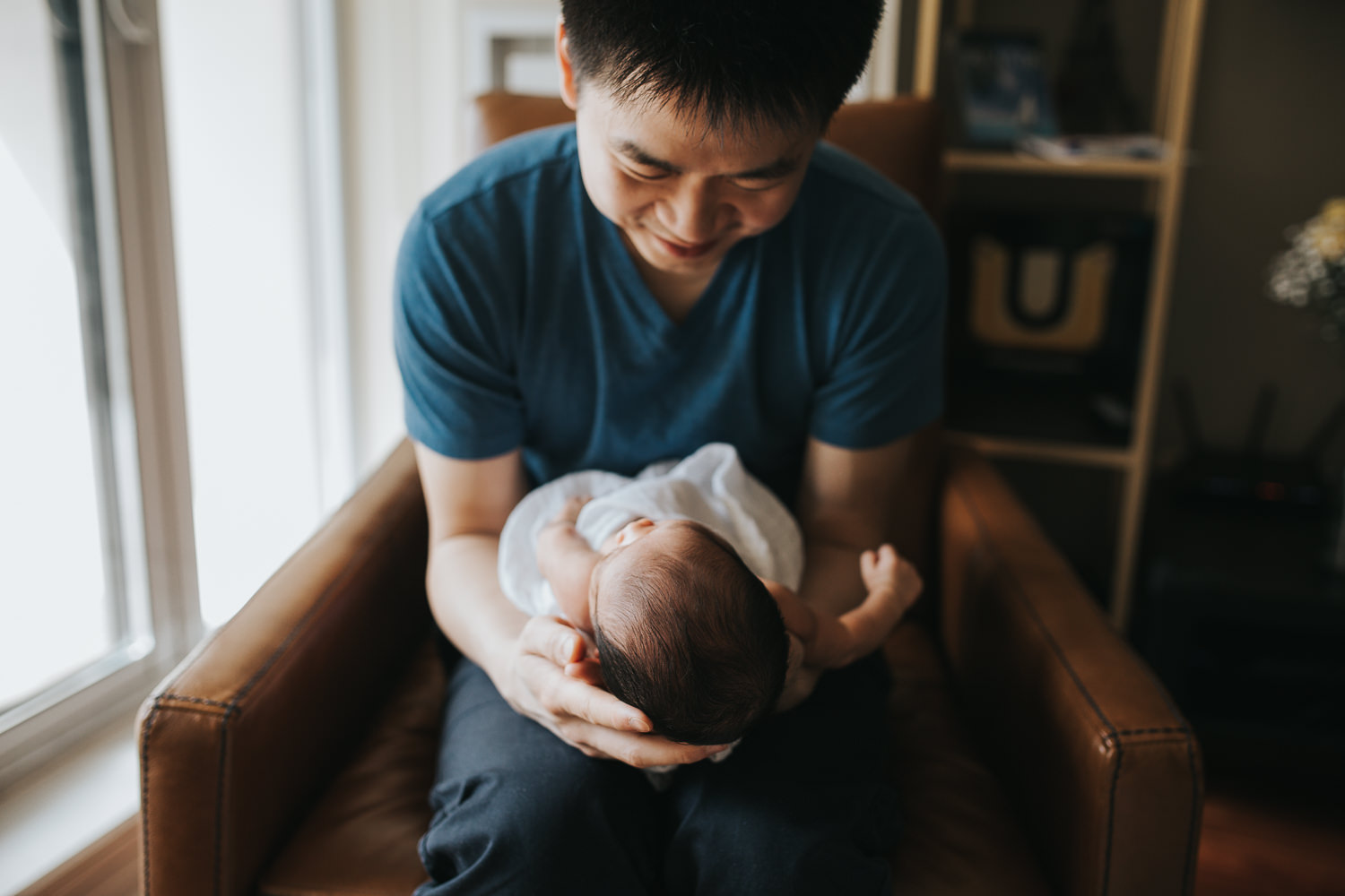 first time dad holding and smiling at 2 week old baby boy - Barrie in-home photography