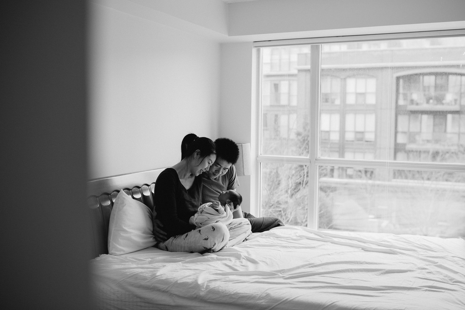 new parents snuggle and look at 2 week old baby boy while sitting in bed - Markham lifestyle photography