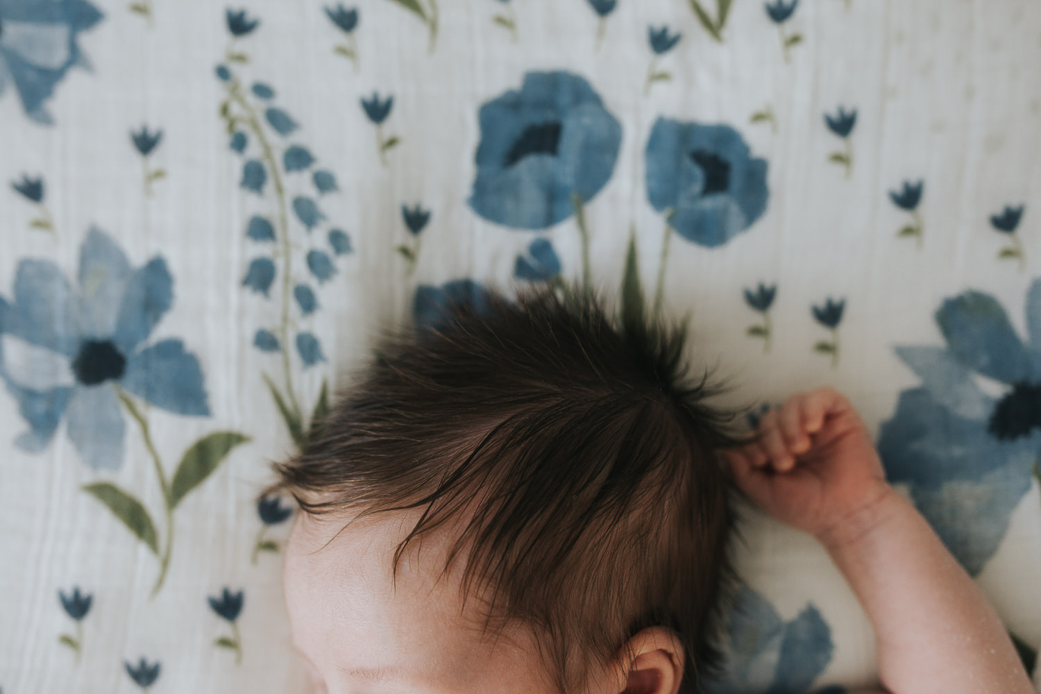 2 week old baby girl with lots of dark hair lying on bed - Newmarket lifestyle photography