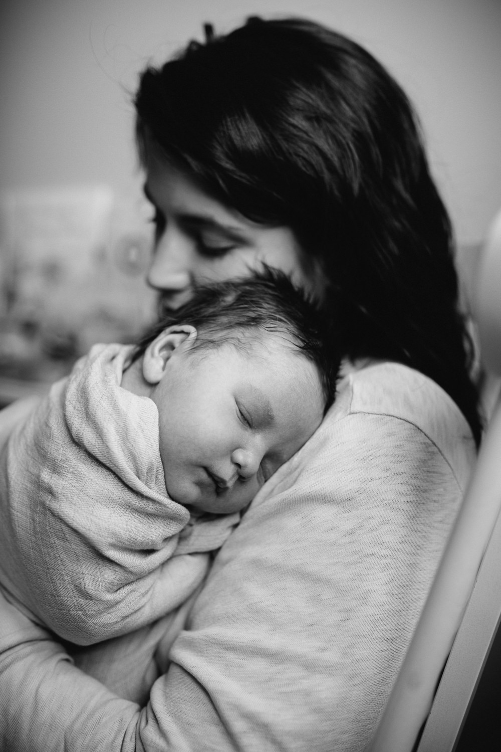 first time mom holding baby girl on shoulder in rocking chair -Markham in-home photography