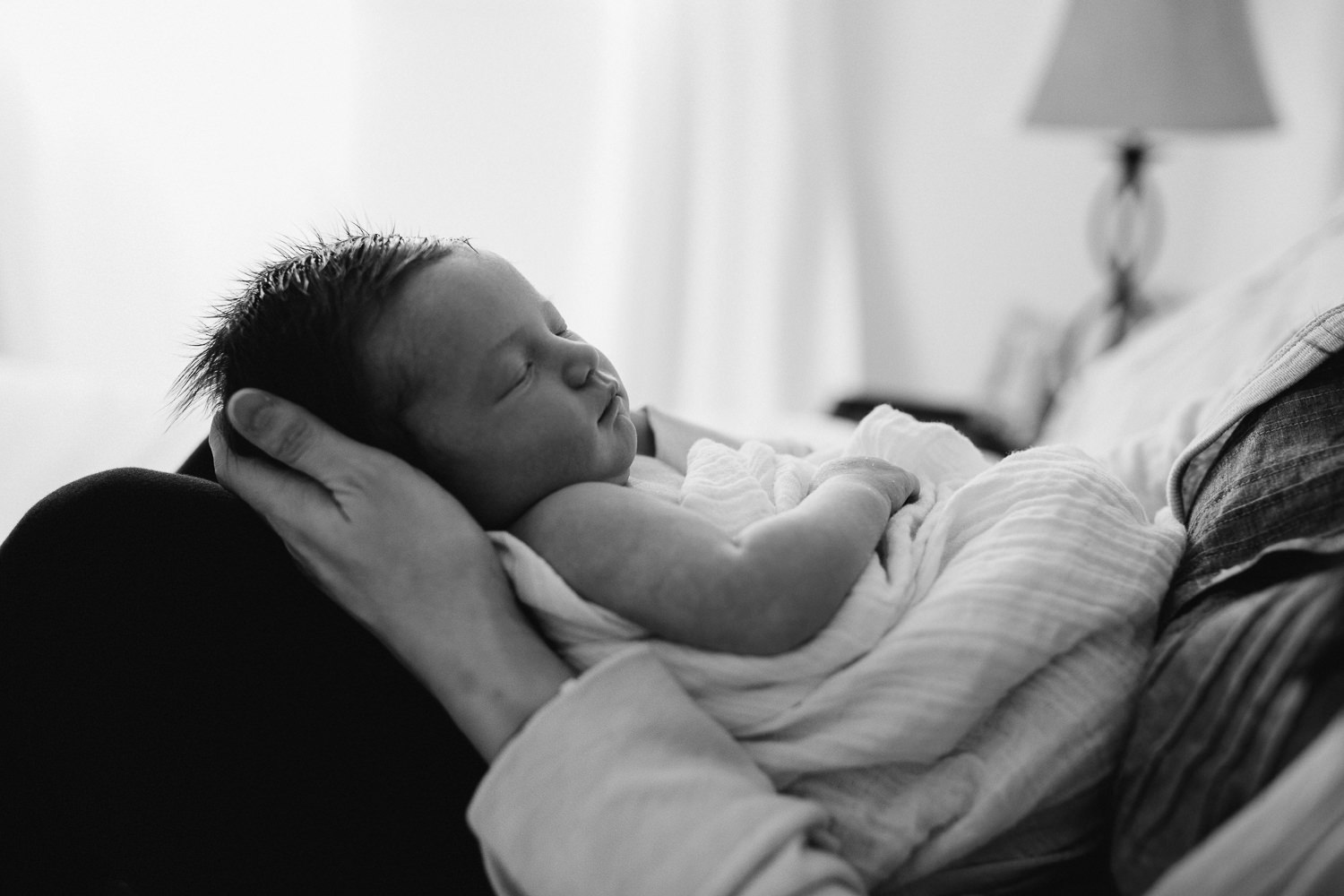 mom sitting on bed holding 2 week old baby daughter who is sleeping - Newmarket lifestyle photography session