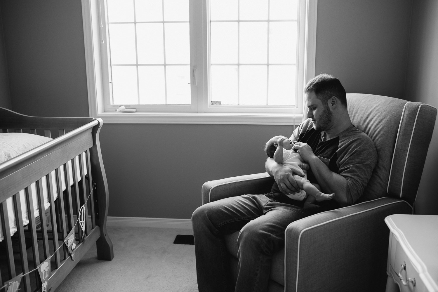 new dad holding 6 week old baby daughter in nursery glider - Stouffville lifestyle photos