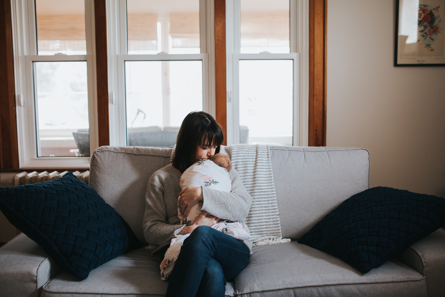 brunette mother holds 5 week old swaddled, sleeping baby girl while sitting on couch - Markham lifestyle photography