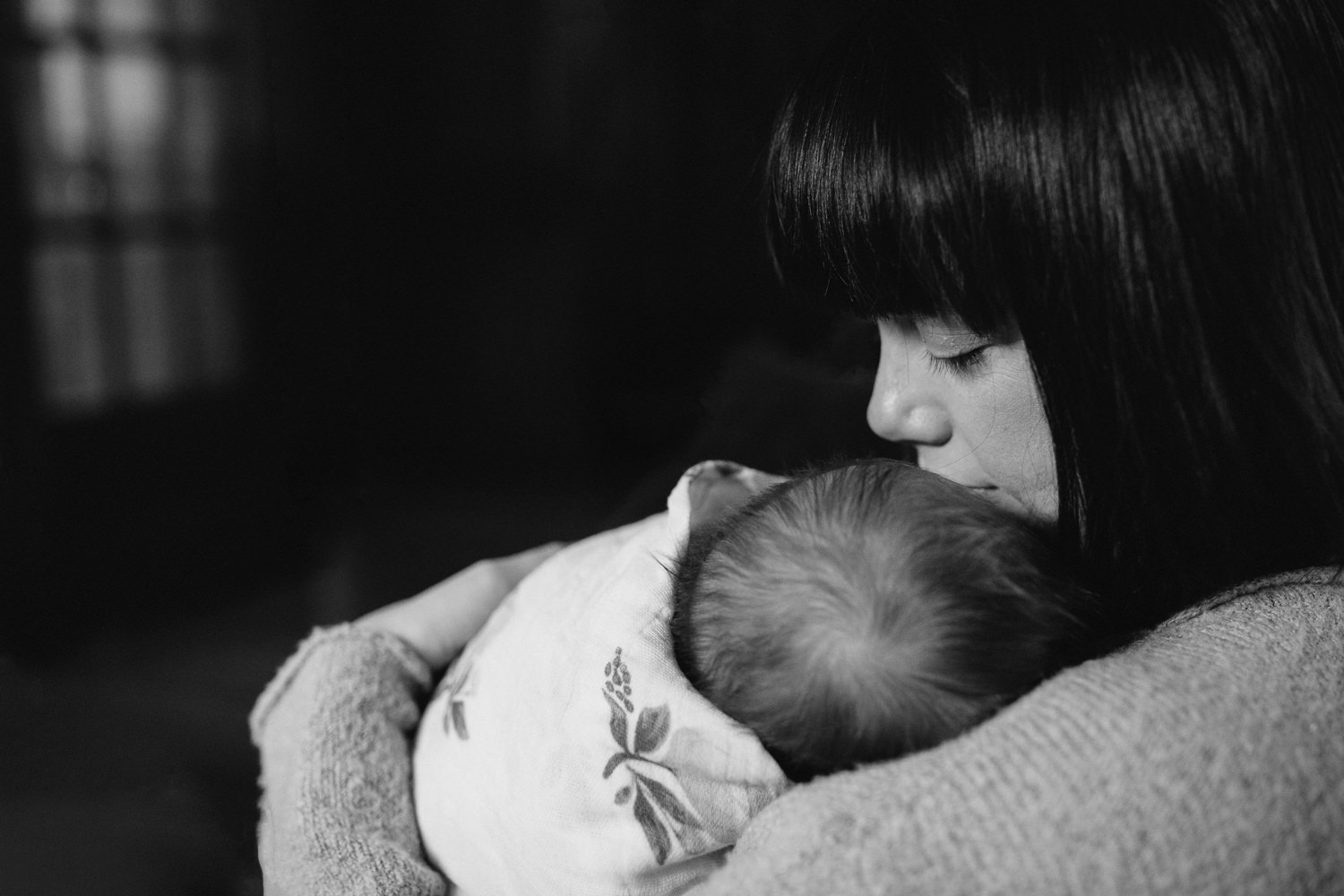 brunette mother holds 5 week old swaddled, sleeping baby girl - Stouffville lifestyle photography