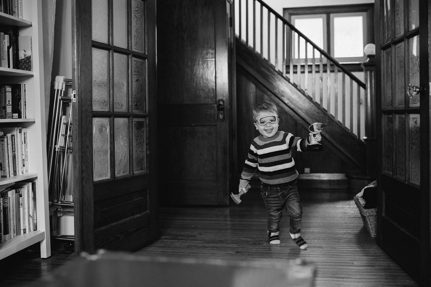 3 year old toddler boy runs into room wearing toy goggles - Newmarket in-home photography