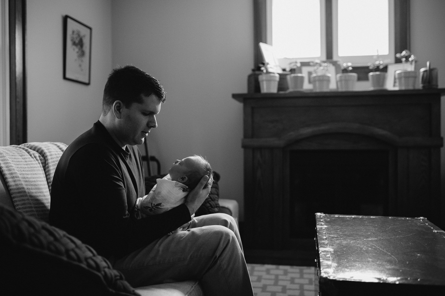 dad looks at 5 week old swaddled baby girl asleep in arms - Markham in-home photography