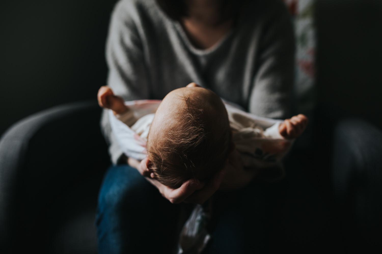 mom holding swaddled, sleeping 5 week old baby girl - Markam lifestyle photos
