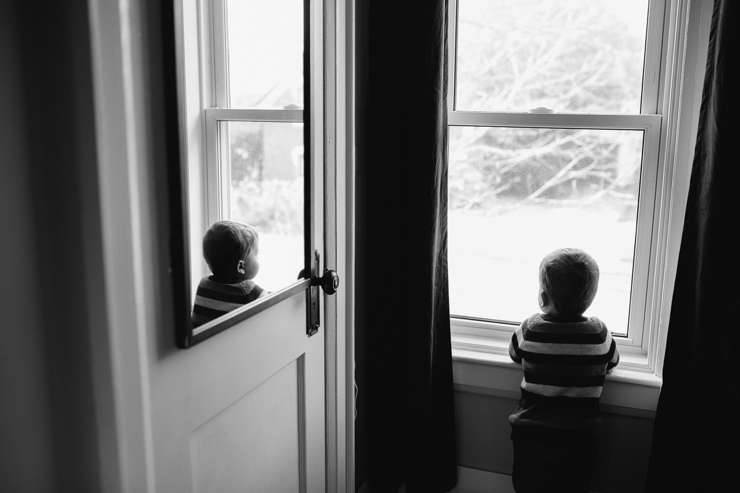 3 year old toddler boy looks out window, can see reflection in mirror - Markham in-home photos