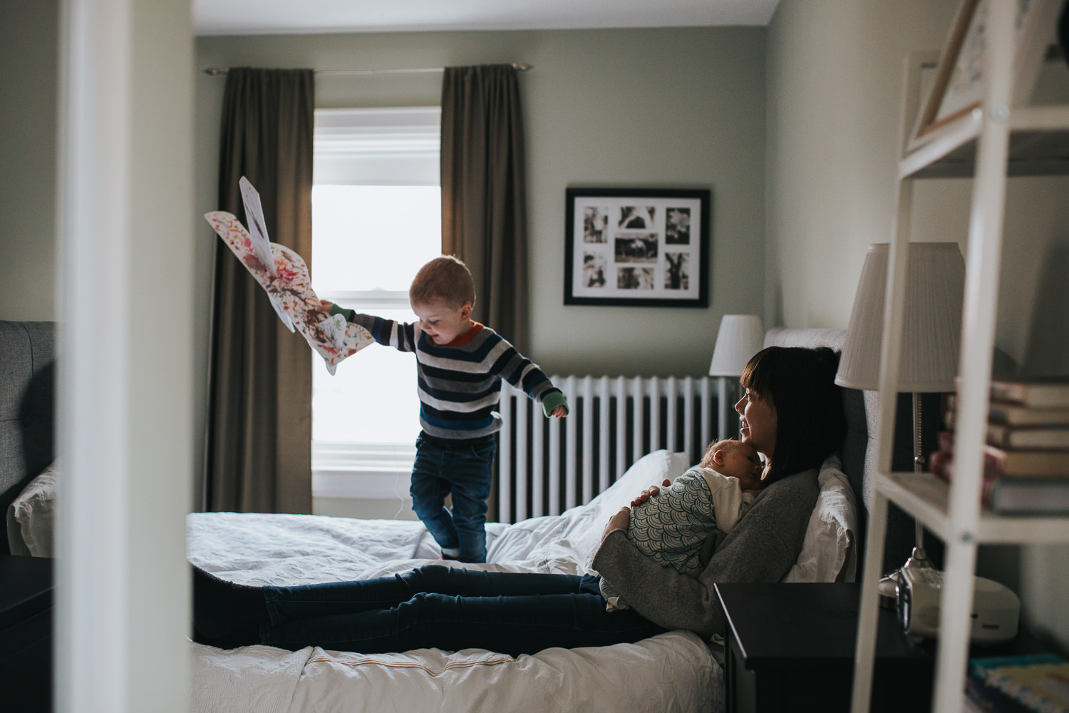 mom sitting on master bed holding baby girl, while toddler son stands on bed flying toy airplane - Markham lifestyle photography