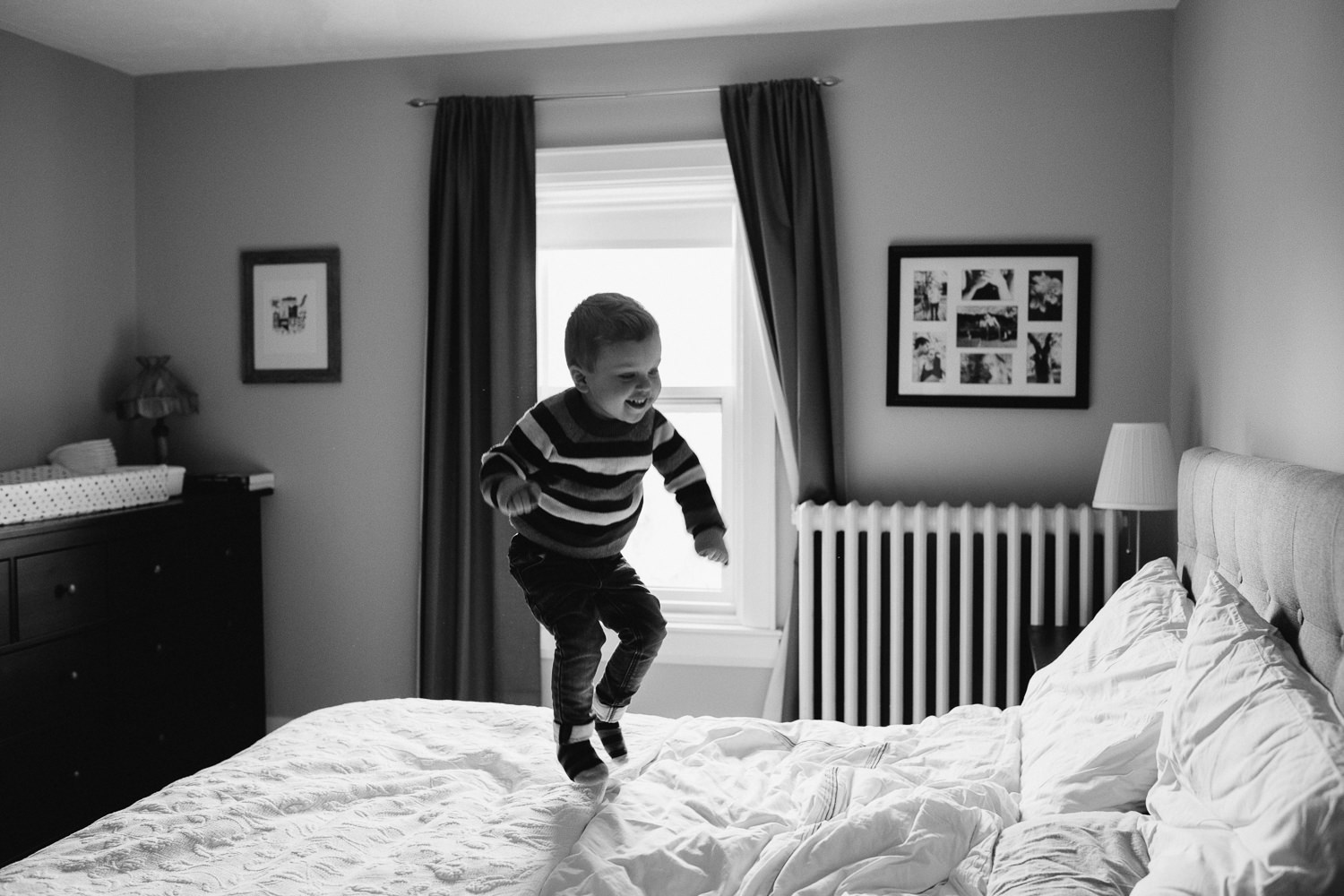 3 year old toddler boy in striped sweater jumps on parent's bed - Markham in-home photography