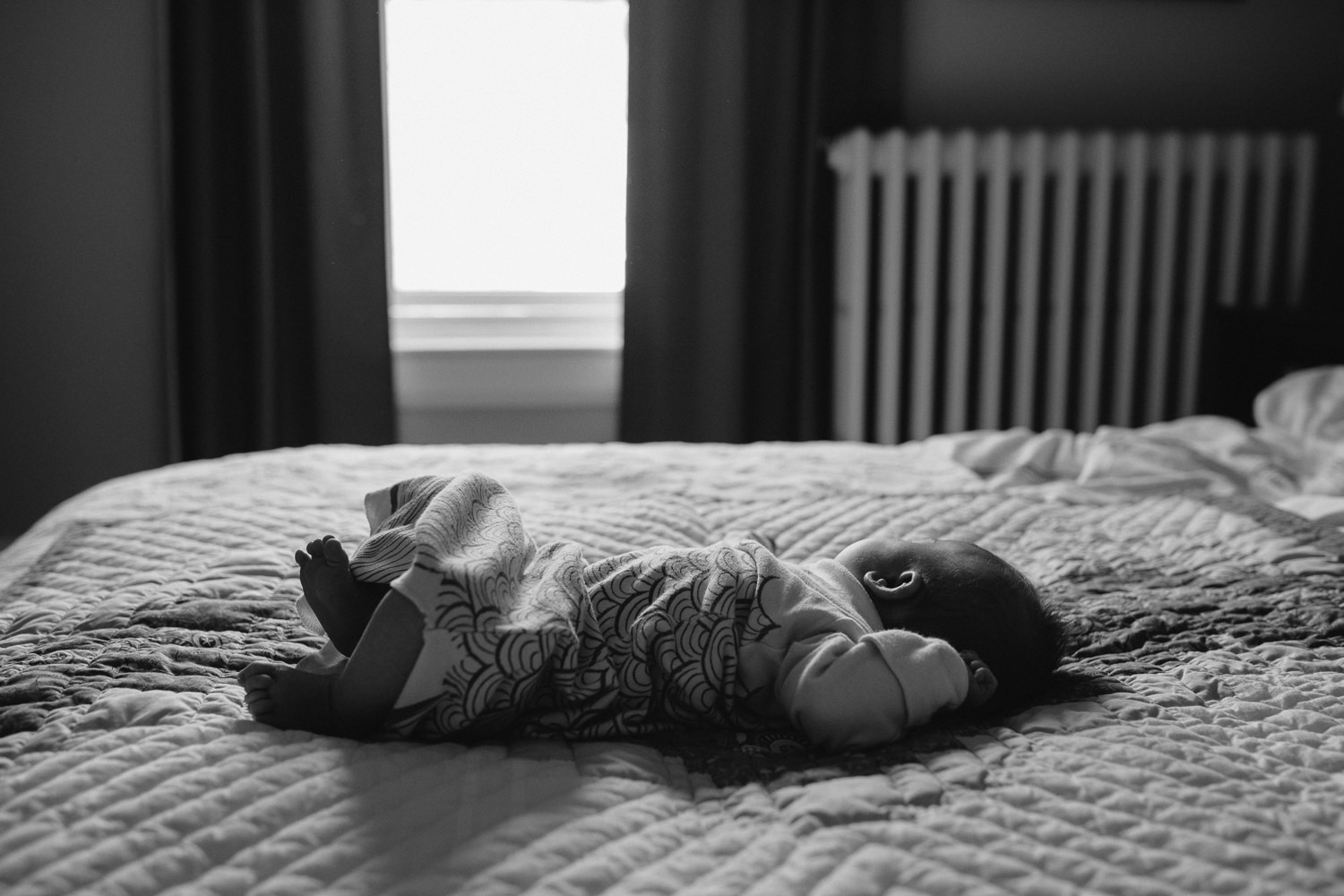 5 week old baby girl lying on parent's bed in master bedroom - Markham lifestyle photos
