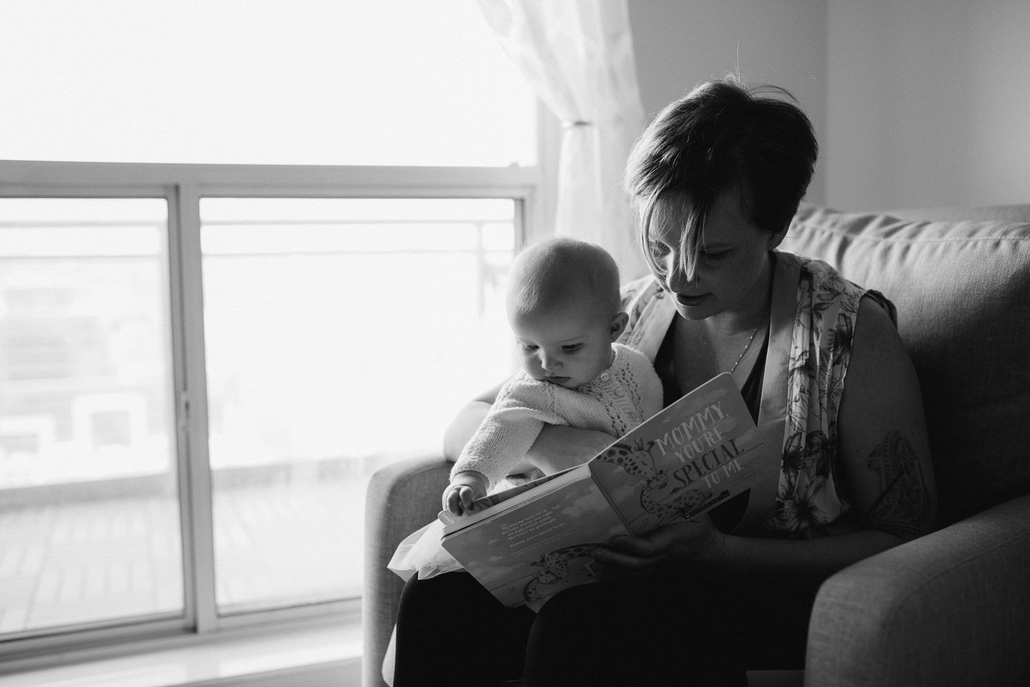 mom sitting in rocking chair reading book to 5 month old baby girl - Newmarket in-home photography