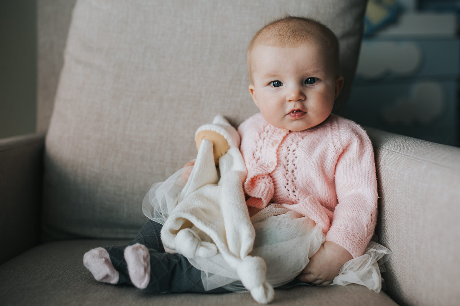 5 month old baby girl in pink sweater sitting on chair looking at camera - Markham lifestyle photography