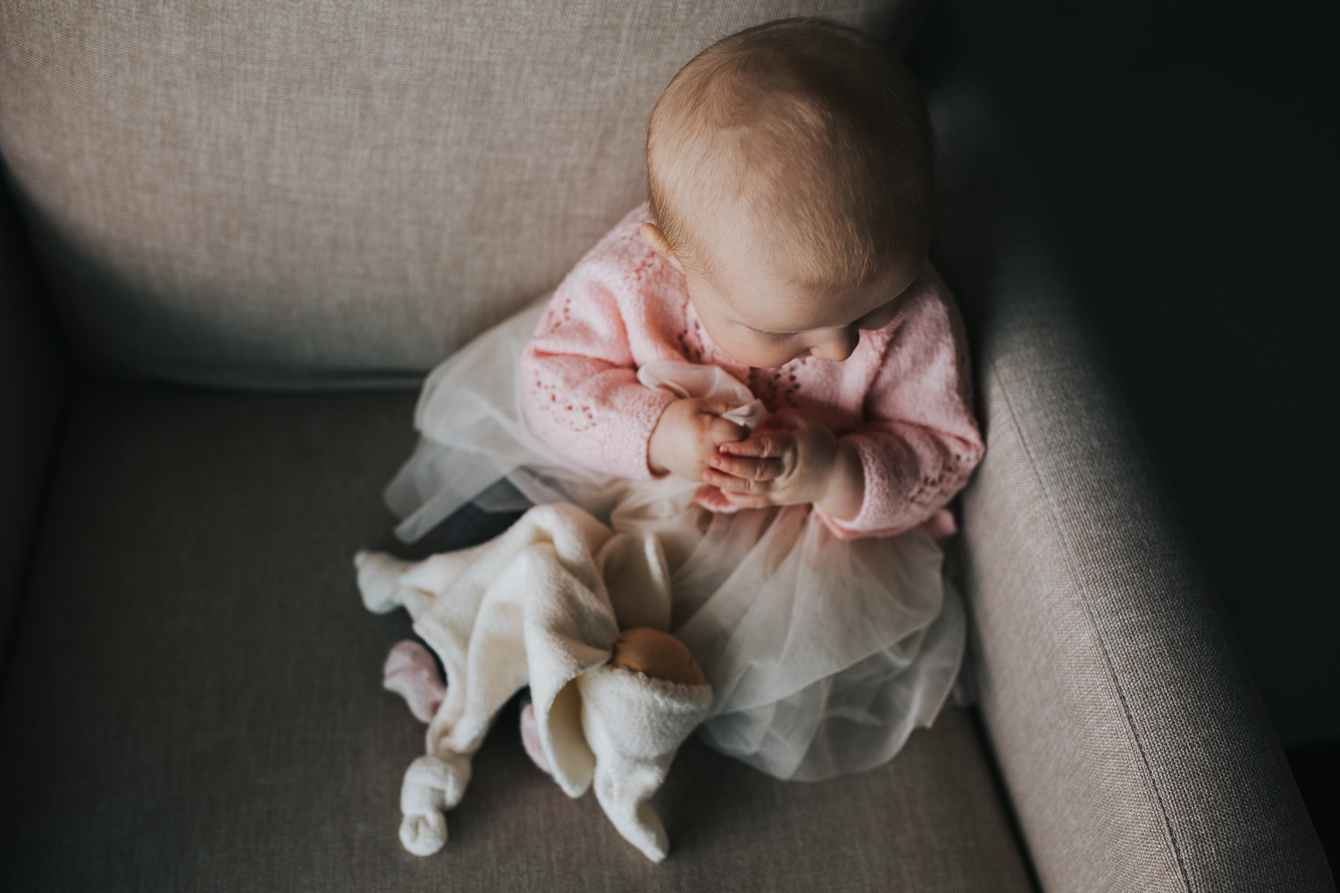 5 month old baby girl in pink sweater sitting on chair with stuffed toy - Barrie lifestyle photography