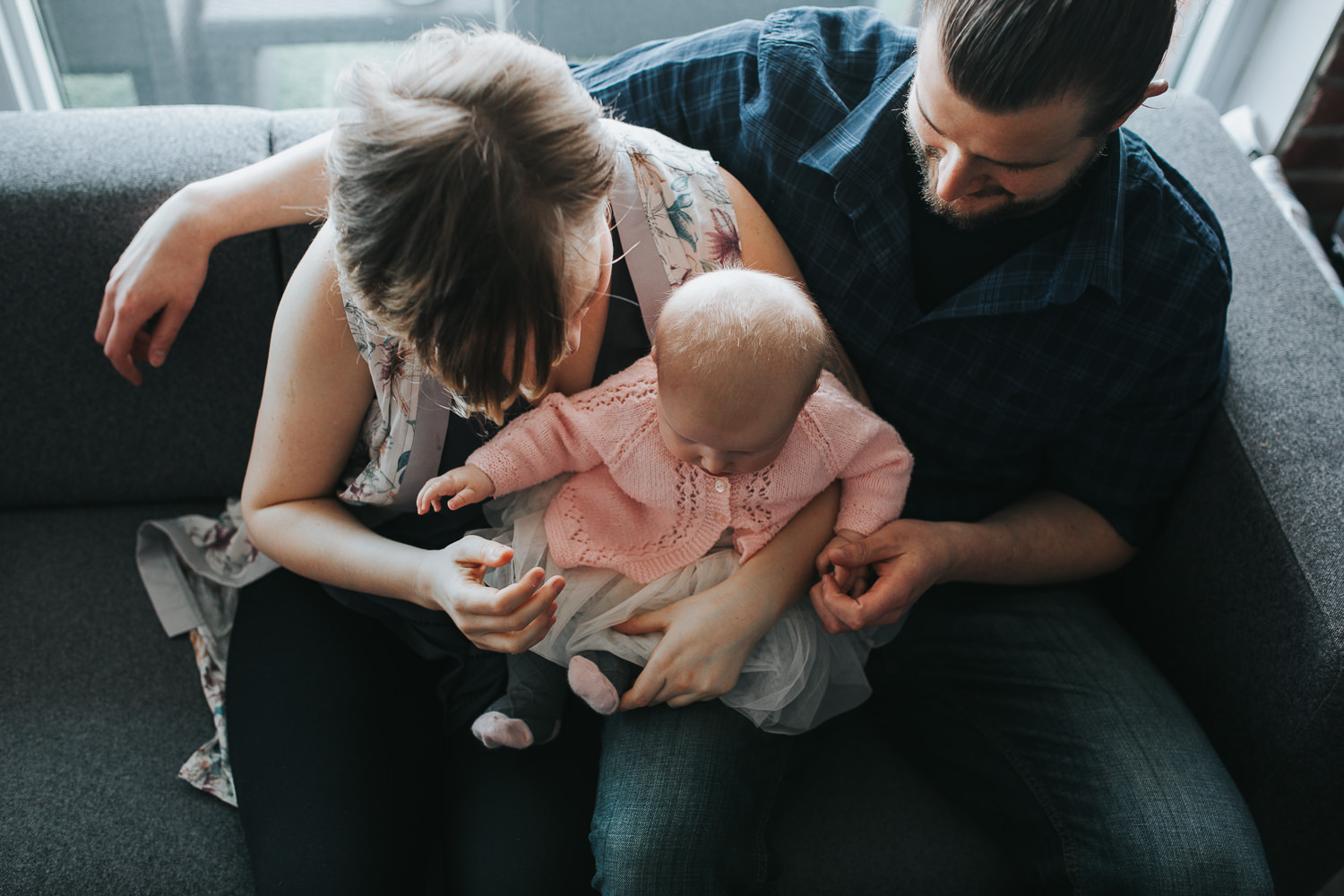 family of 3 sitting on couch,  5 month old baby girl sitting on mom's lap - Stouffville lifestyle photos