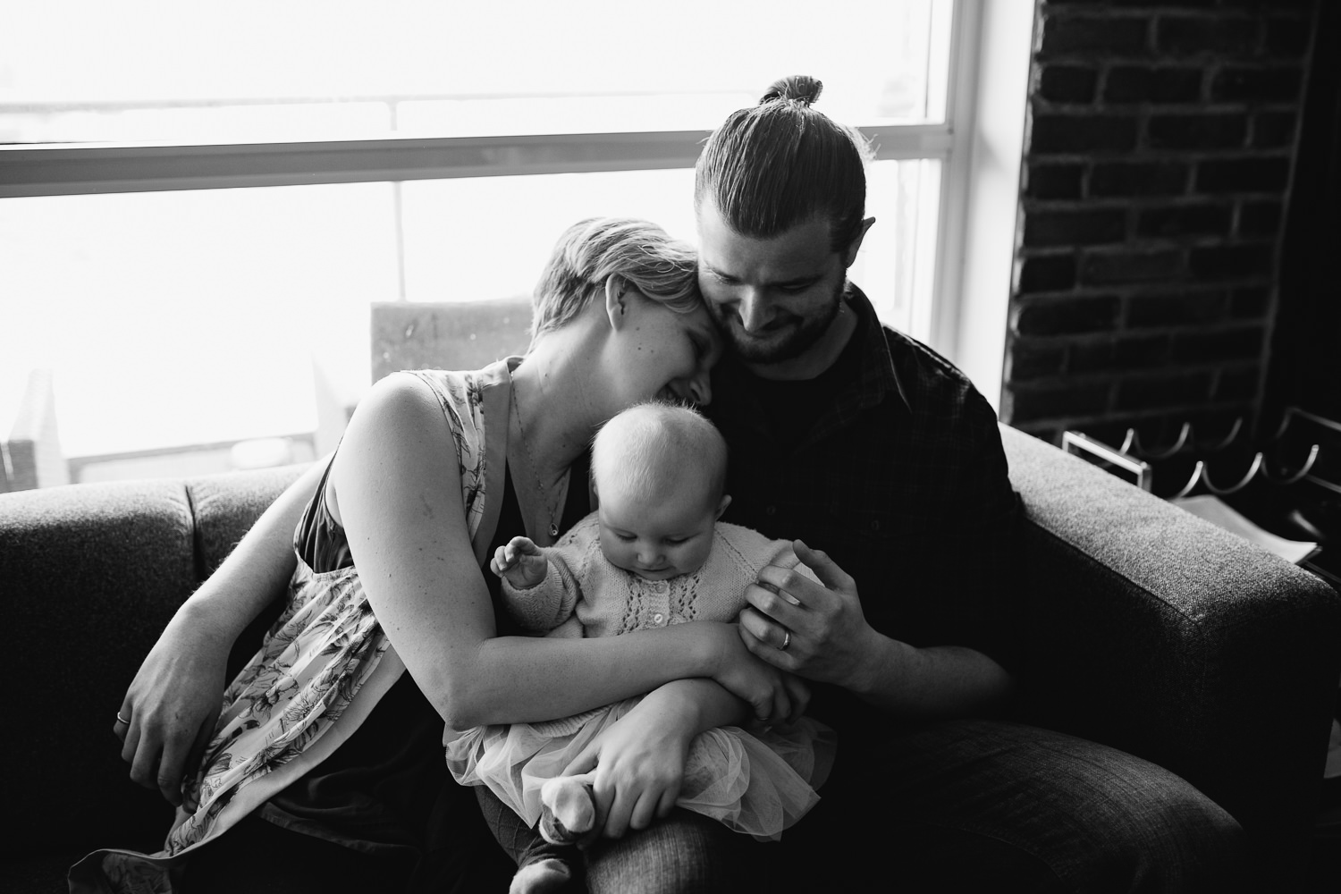 family of 3 sitting on couch, husband and wife snuggle with 5 month old baby girl on mom's lap - Markham lifestyle photos