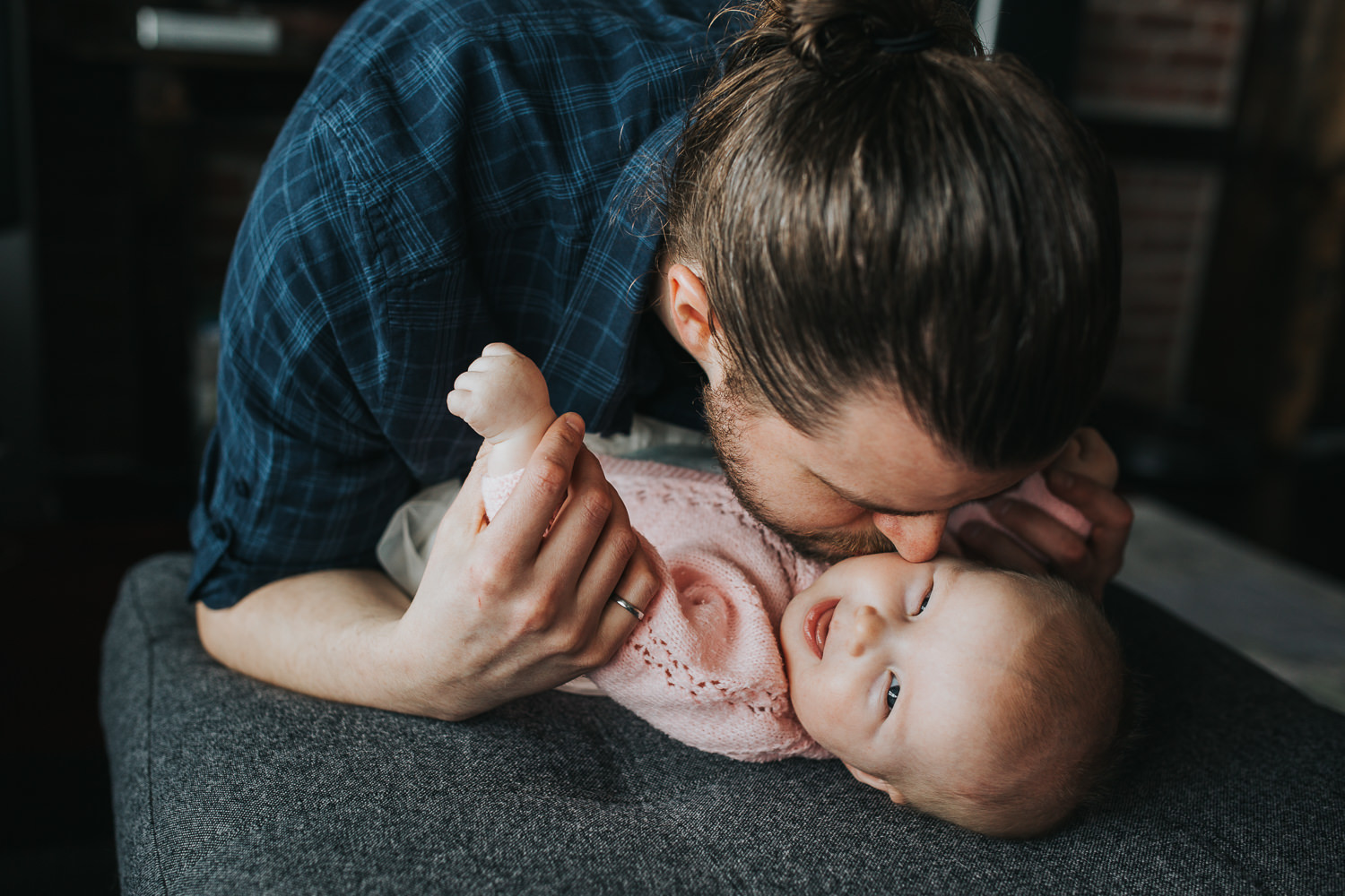5 month old baby girl laughing, lying on couch as dad kisses her - Stouffville lifestyle photography