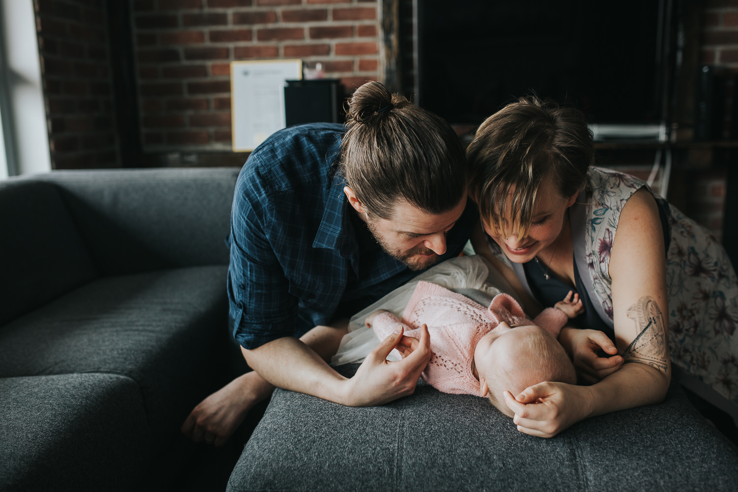 parents looking and smiling at 5 month old baby girl lying on couch - Stouffville lifestyle photography
