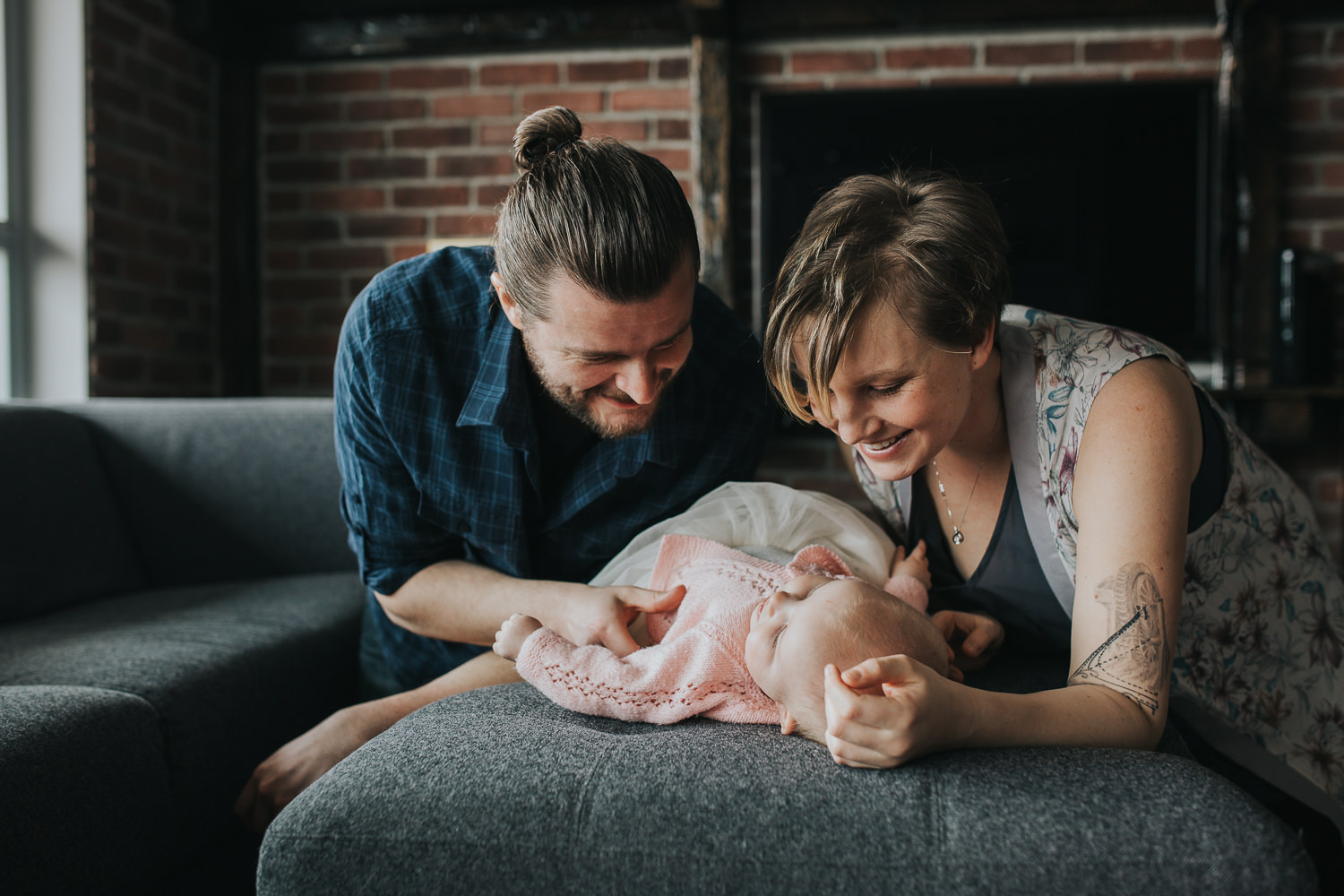 parents looking and smiling at 5 month old baby girl lying on couch - Newmarket lifestyle photography