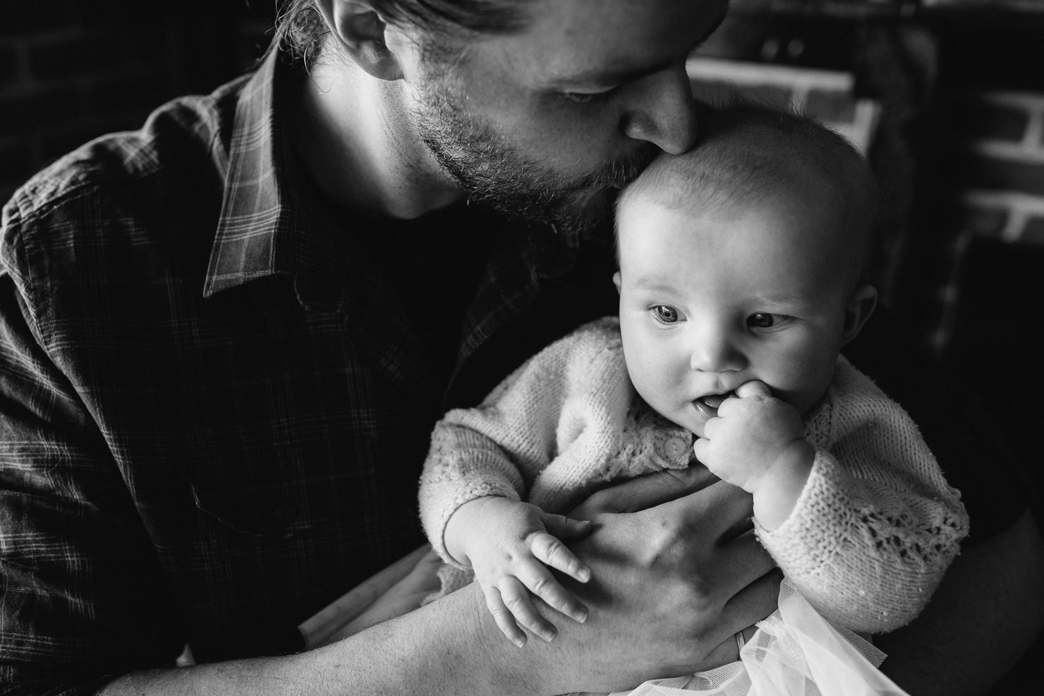 dad holds and kisses 5 month old baby girl in pink sweater who is chewing on her hands - Newmarket in-home photography