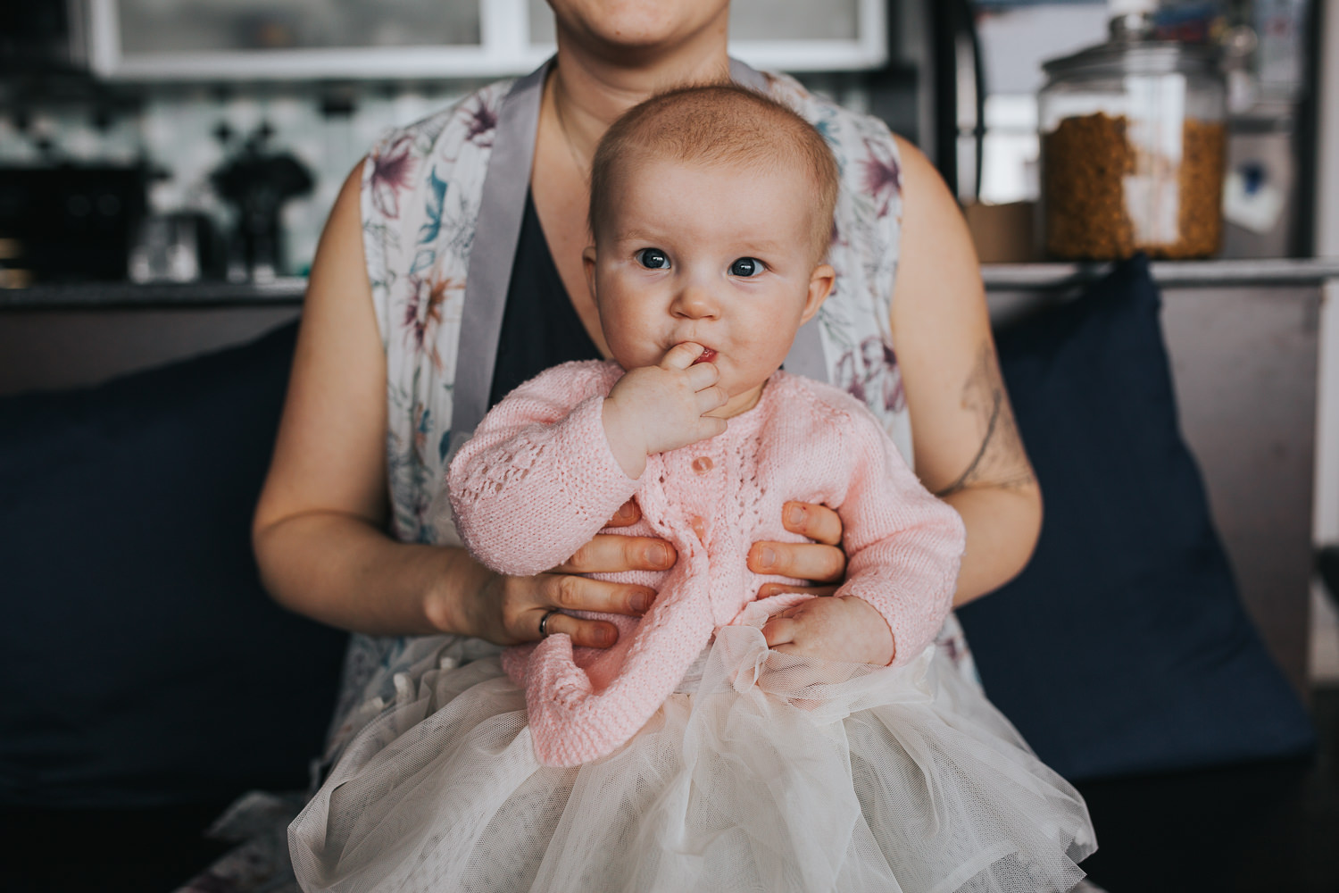 5 month old baby girl in pink sweater and tutu sitting in mom's lap looking at camera - Stouffville in-home photography