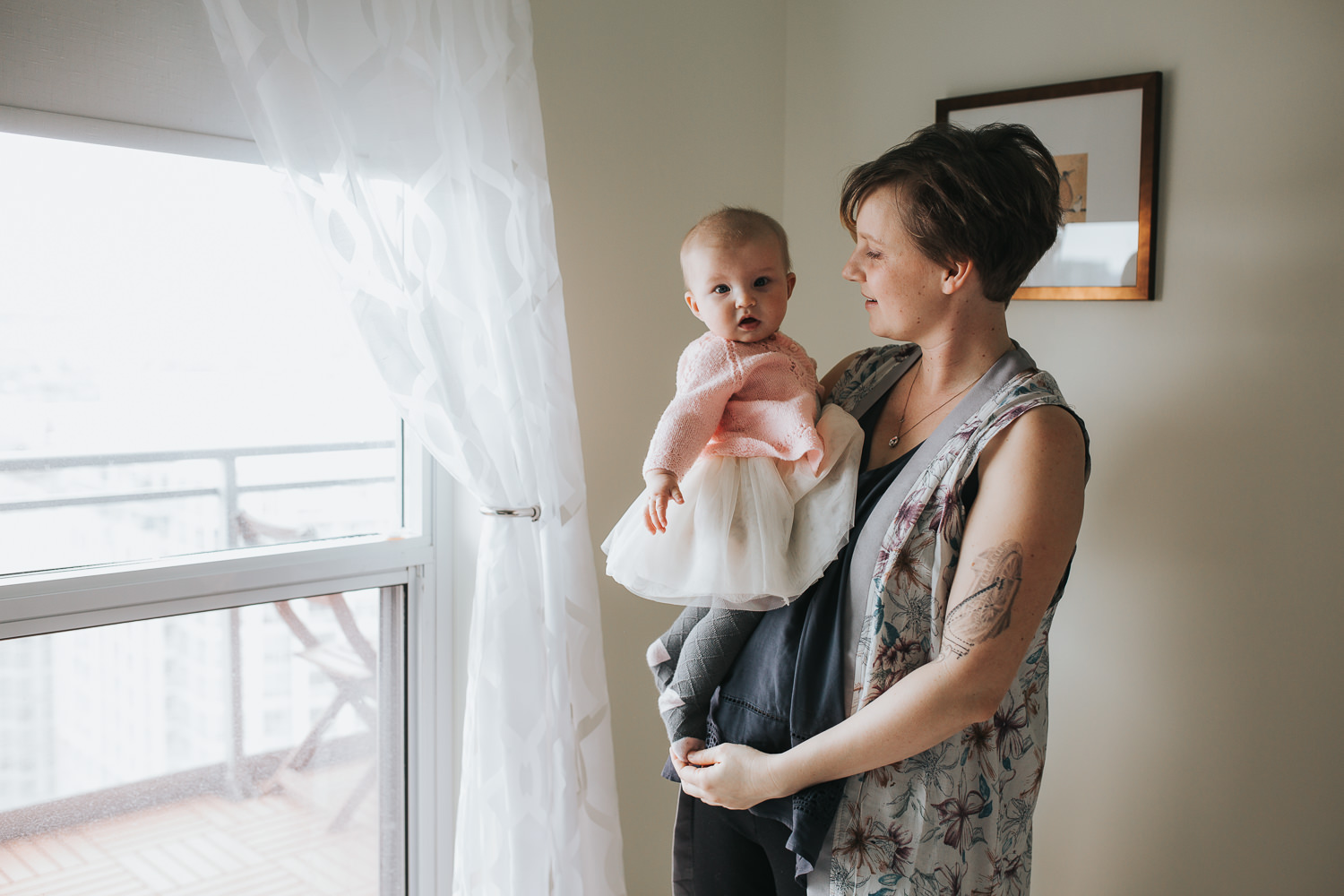 mom holding and looking at 5 month old baby daughter in pink sweater, baby looking at camera -  Stouffville lifestyle photos