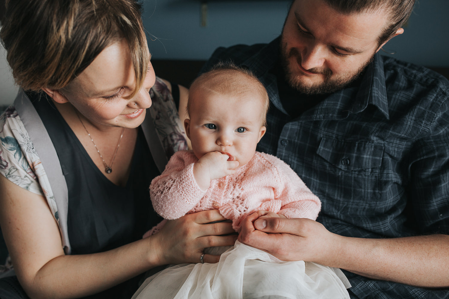 mother and father holding and looking at 5 month old baby girl in pink sweater and tutu who is chewing on her hand - Barrie lifestyle photos