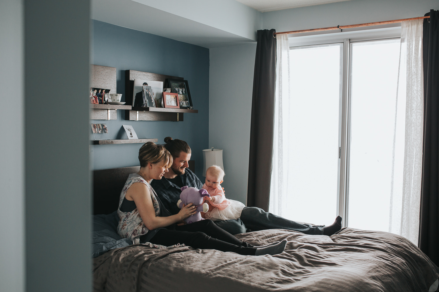 parents sitting on master bed holding and playing with 5 month old baby girl in pink sweater and tutu - Stouffville in-home photos