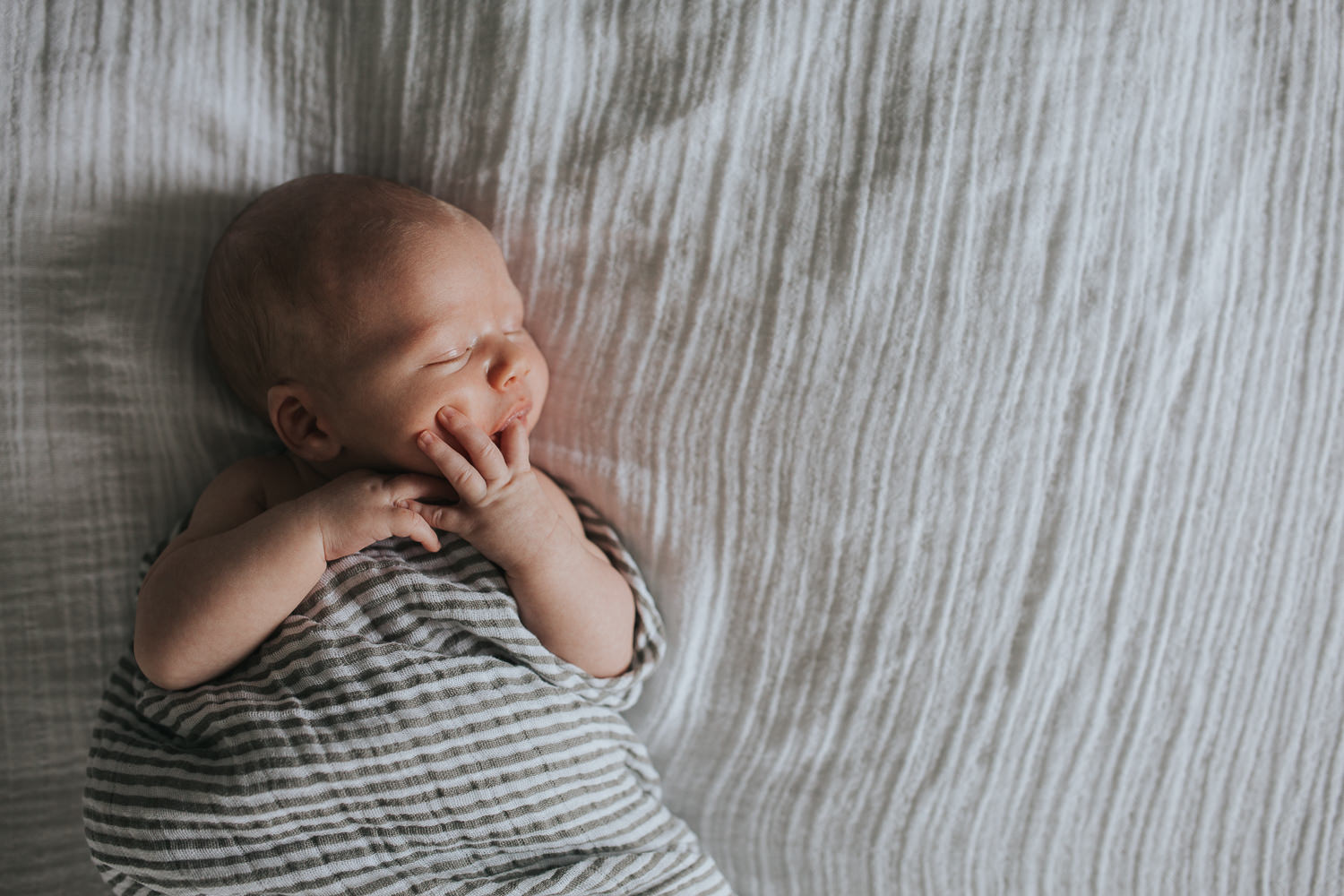 2 week old baby boy asleep, lying on bed in striped neutral swaddle with hand in mouth - Markham lifestyle photography