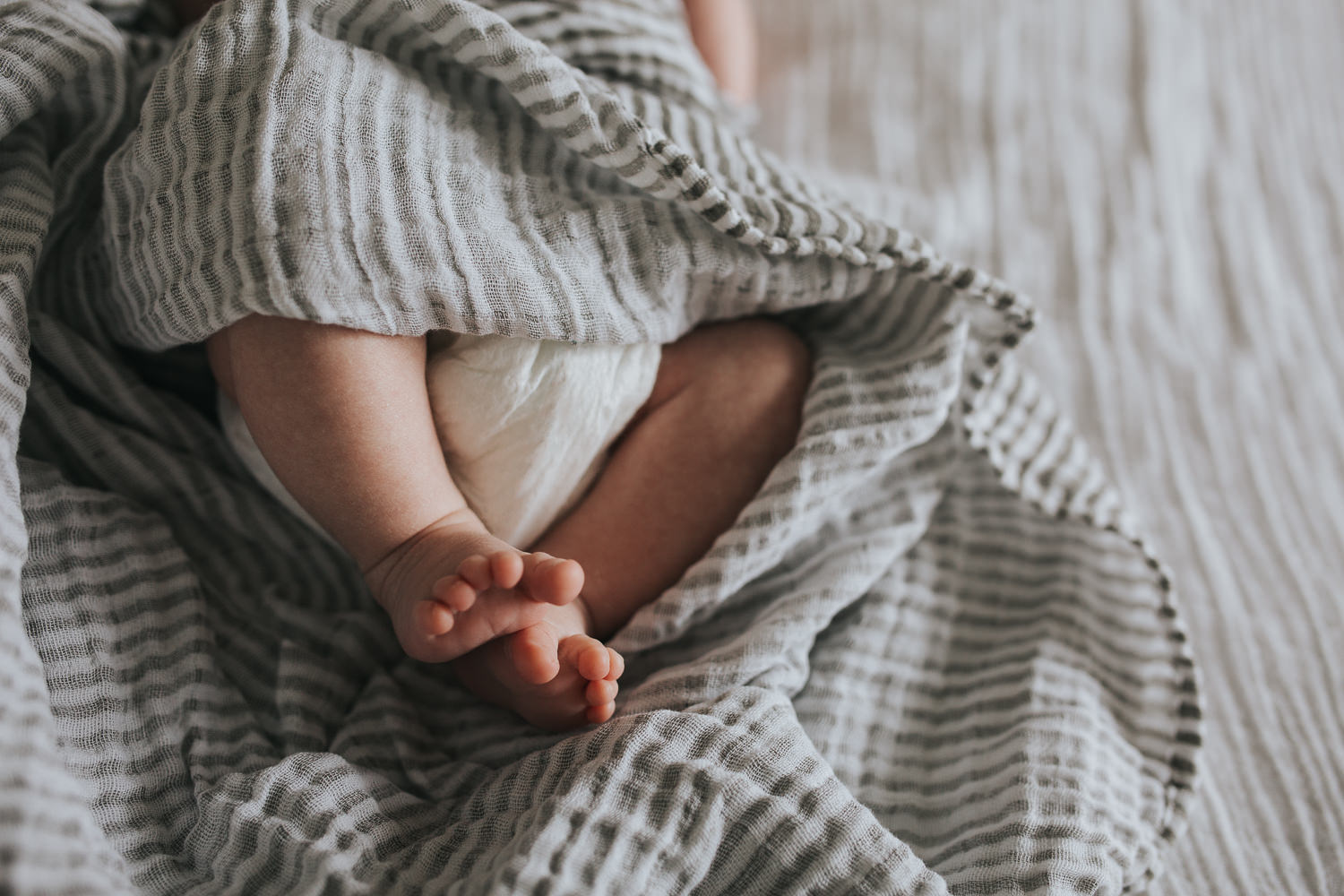close up of 2 week old baby boy's feet, lying on white bed in striped neutral swaddle - Barrie lifestyle photography