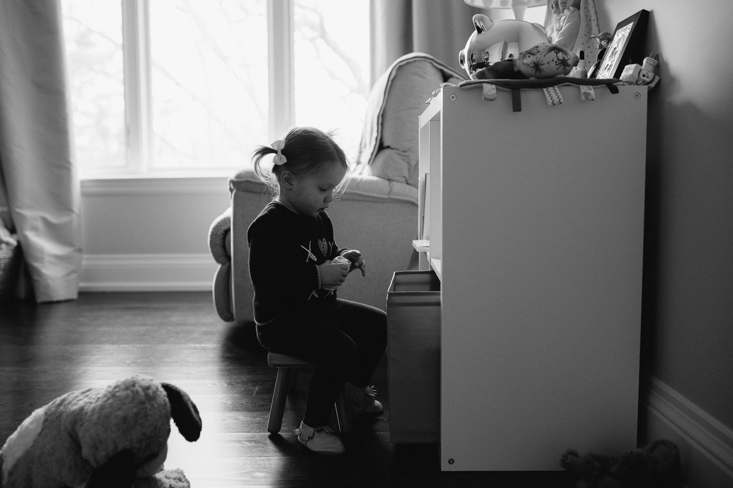 2 year old toddler girl playing in bedroom, pulling socks from basket - Newmarket in-home photos
