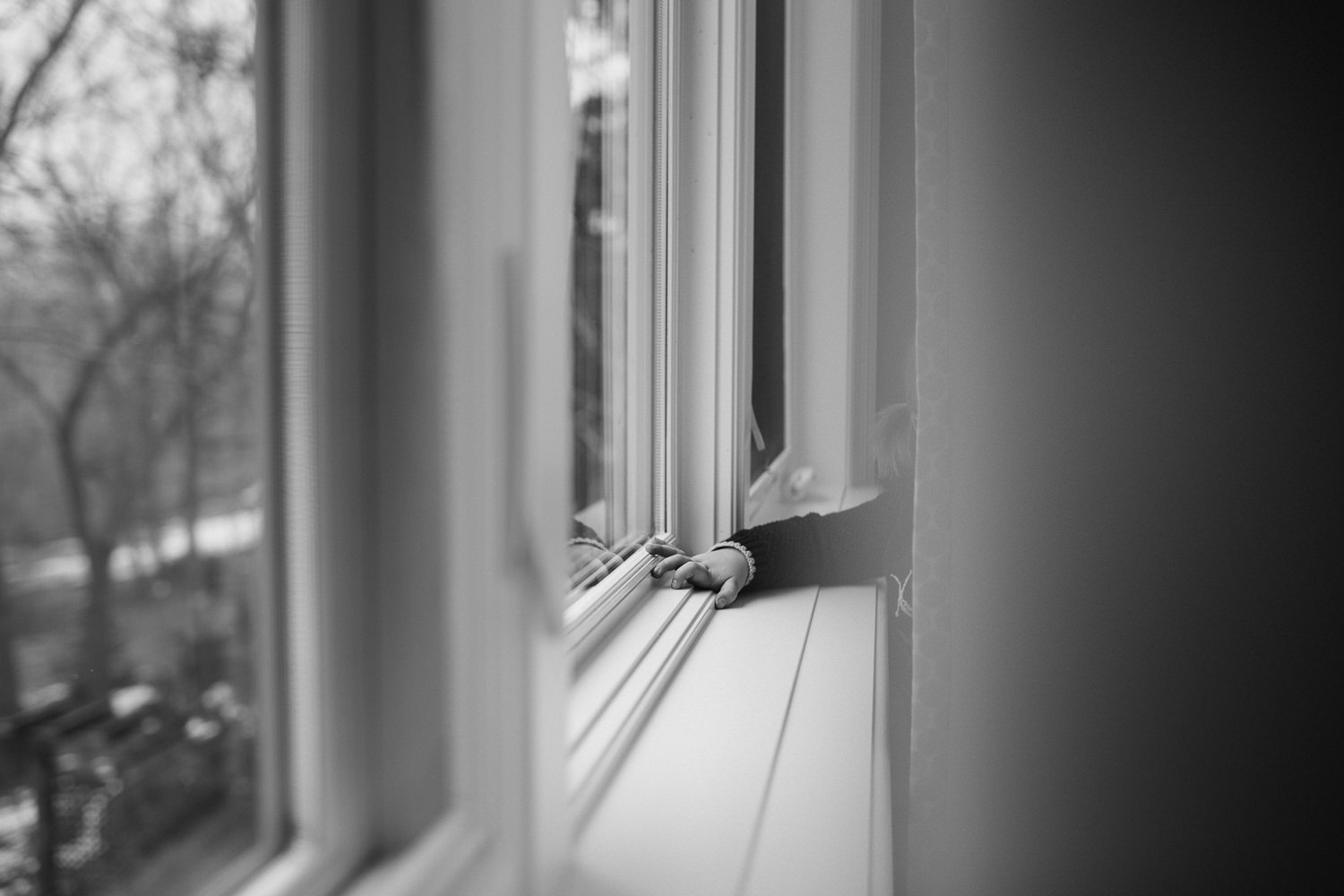 2 year old toddler girl's hand reaching through curtains, resting on windowsill - Markham lifestyle photography