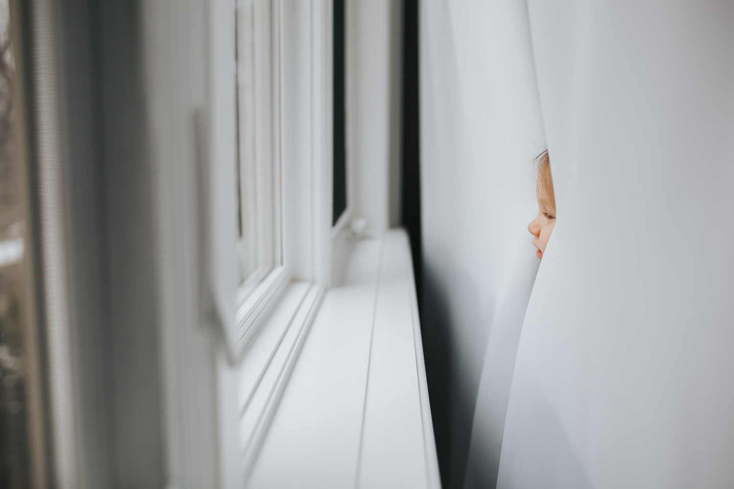 2 year old toddler girl's face peeking through curtains - Barrie lifestyle photography