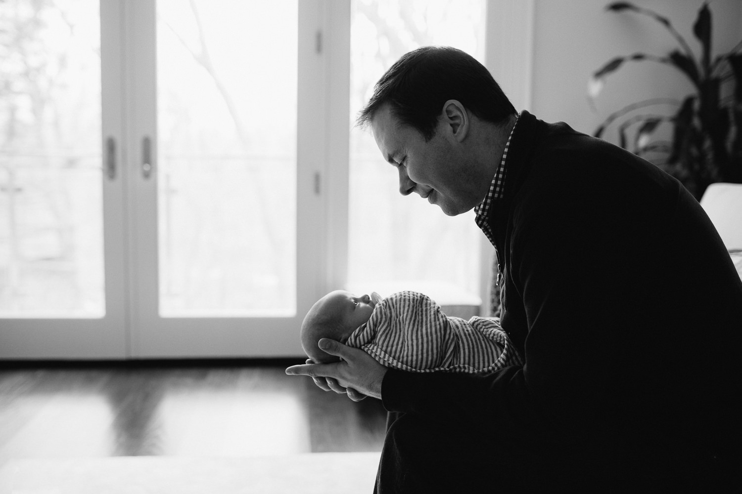 dad leaning forward, holding and looking at 2 week old baby boy - Markham lifestyle photos