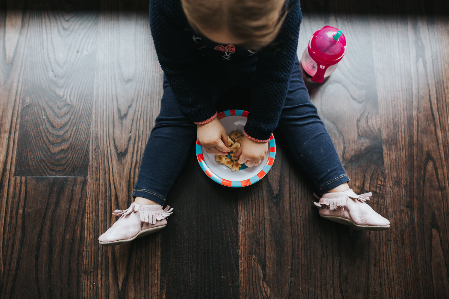 2 year old toddler girl sitting on floor eating snack from a bowl - Stouffville lifestyle photos