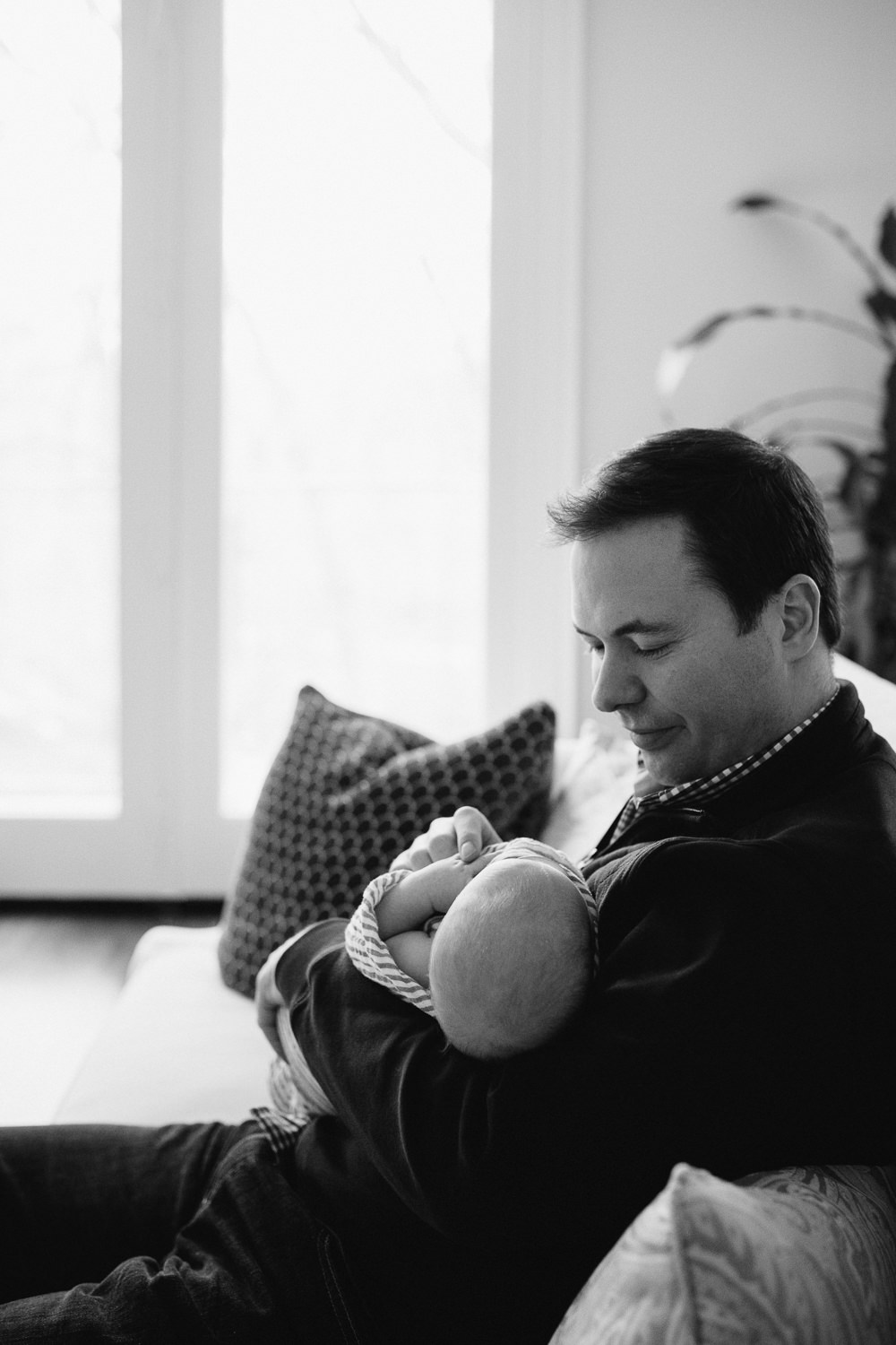 dad holding and looking at 2 week old baby boy - Barrie lifestyle photos