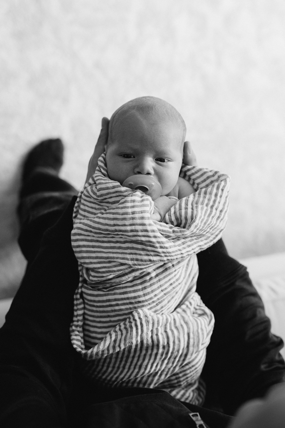 2 week old swaddled baby boy with soother in mouth looking at camera as father holds him - Newmarket in-home photos