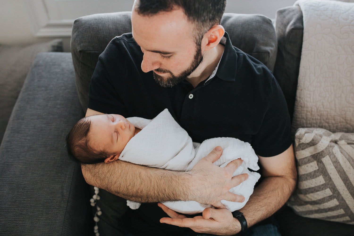 new dad sitting on couch holding and looking at sleeping 2 week old baby son -  Markham in-home photos