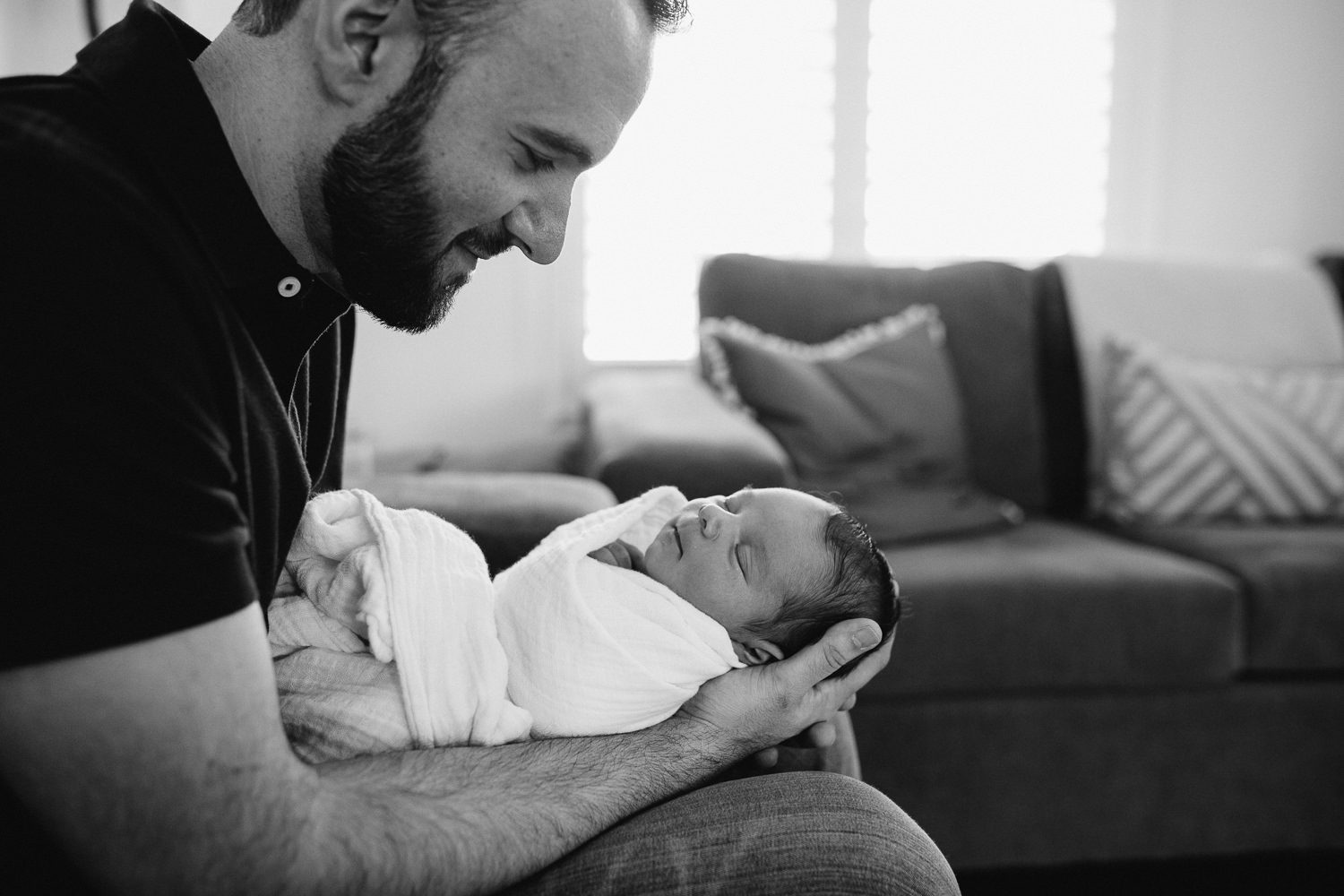 new dad sitting on couch holding and looking at sleeping 2 week old baby boy -  Barrie in-home photos