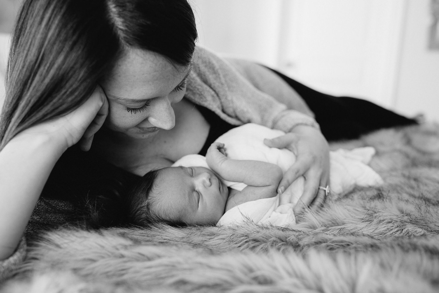 new mom lying on bed looking at sleeping, swaddled 2 week old baby boy - Barrie In-Home Photography
