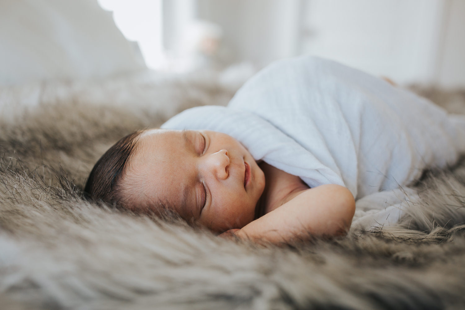 2 week old baby boy asleep on parent's bed in white swaddle - Newmarket lifestyle photos